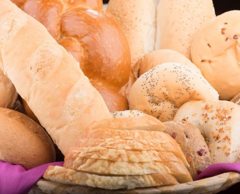Tasty Pastry Tasty Treats: Overflowing Basket of a Variety of Bread (rolls, sliced, bagels, plaited)