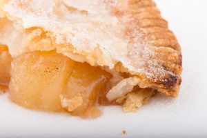 close-up of a slice of apple pie (shows flaky crust and seasoned apples filling)