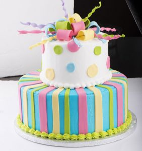 Two-tier cake with pastel colors; 1st tier: stripes, 2nd tier: polka dots, topped with edible ribbon