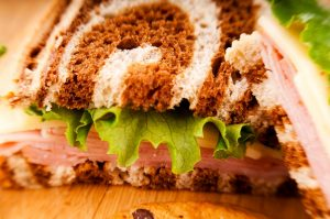 Tasty Pastry Take Home Meals: Close up on Sandwich with lettuce, meat & cheese on marbled rye