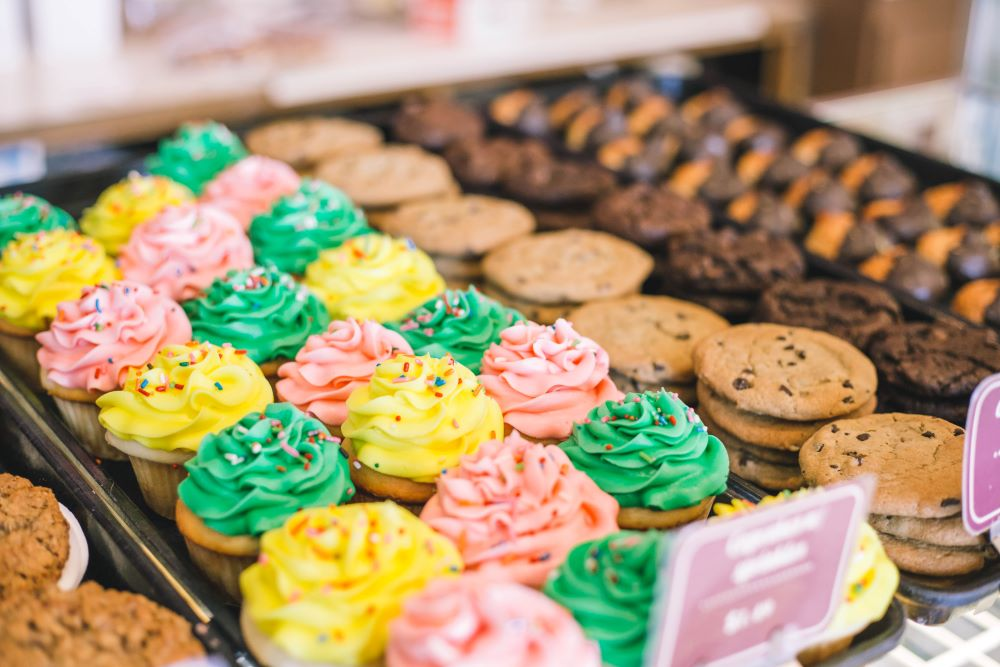 Tasty Pastry Display showing assortment of baked goods including: cupcakes with green, yellow or pink icing & sprinkles and cookies (chocolate chip, chocolate, oatmeal raisin)